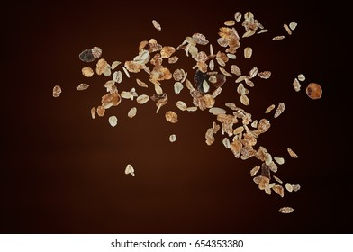 muesli flying or dropping against brown background