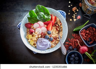 Muesli and fresh berries in ceramic bowl as healthy breakfast concept with ingredients arranged to the side. Viewed from above, over dark matte table surface
