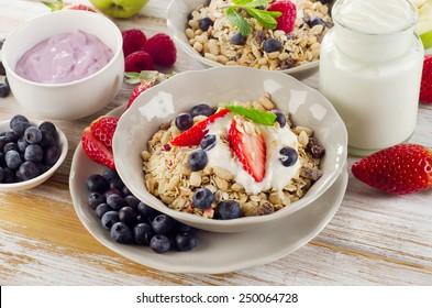 Muesli,  fresh berries and yogurt for healthy breakfast  on wooden table