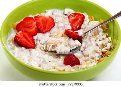 Muesli with fruit and berries in a green cup on a white background.