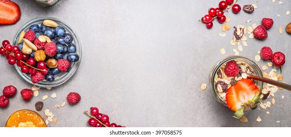 Muesli, nuts and berries. Breakfast preparation. Granola with fresh berries in jar on stone background, top view, banner.  Healthy food and Clean Eating concept