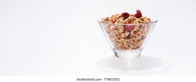 Muesli with red fruits in a glass bowl isolated on white