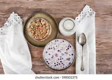 Muesli set with a bottle of milk on wooden table, view from above.