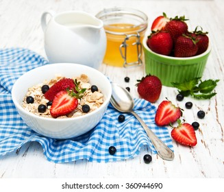 Muesli with strawberries on a old wooden background