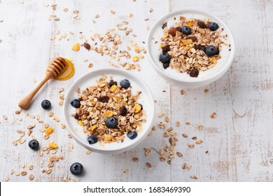 Muesli with yoghurt in a bowl on white wooden background