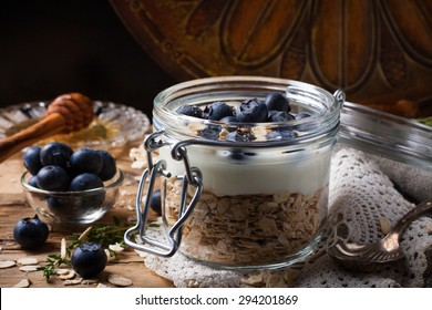 Muesli with yogurt and blue berries in glass jar on dark background. Healthy breakfast. Health and diet concept. Law key. Selective focus.