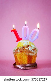 Muffin with burning birthday candles as number one hundred on pink background