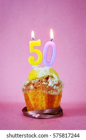 Muffin with burning birthday candles as number fifty on pink background