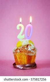 Muffin with burning birthday candles as number twenty on pink background
