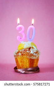Muffin with burning birthday candles as number thirty on pink background