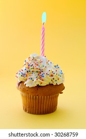 Muffin with candle isolated on yellow background