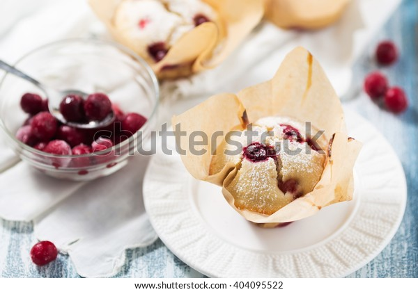 Muffin with cherries on white plate, wooden blue table