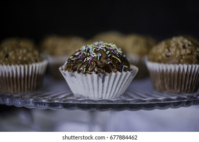 Muffin with chocolate and colorful topping on glass cake-stand.