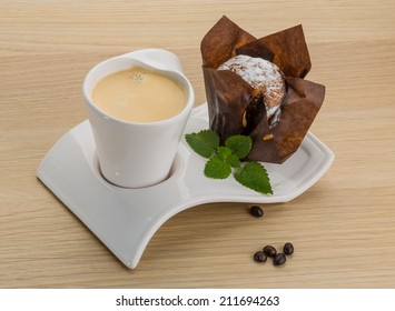 Muffin and coffee on the board with mint