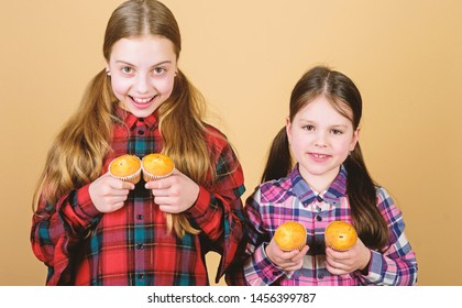 Muffin fight. Small children happy smiling with quickbread muffins. Happy little girls baking breakfast muffins at home. Enjoying their favorite muffin flavor.