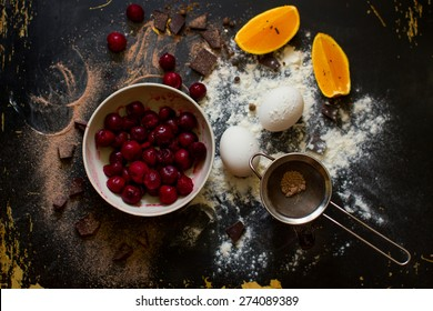 Muffin ingredients: the frozen cherry in a plate, orange segments, eggs, flour on a dark wooden background