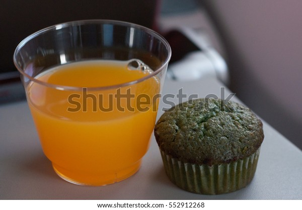 muffin and orange juice on the plane portable table .