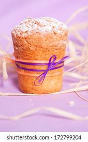 muffin with purple ribbon on purple background. macro