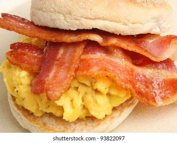 Muffin with scrambled eggs and bacon.