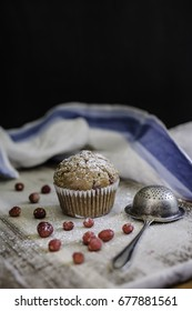 Muffin with wild strawberries and metal strainer on the wooden board.