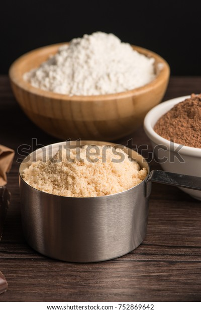 Muffins baking ingredients on wooden table.