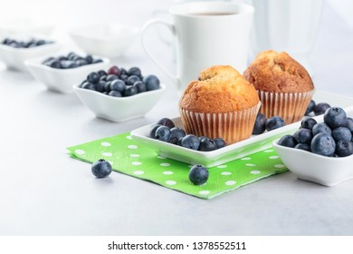 Muffins and blueberry on white kitchen table.