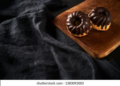 Muffins with chokolate glaze on old rustic wooden board on dark fabric background, copy space for text