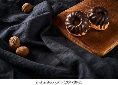 Muffins with chokolate glaze on old rustic wooden cutting board and walnuts on dark fabric background, copy space for text
