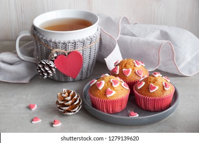 Muffins decorated with sugar hearts and a cup with red heart on light gray background. Valentine's day or winter birthday concept.