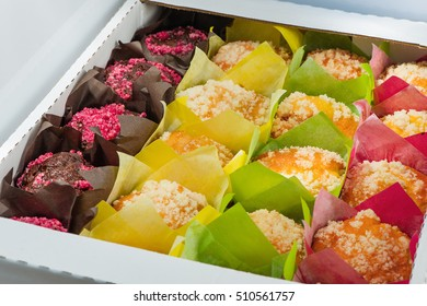 The muffins of different color packed into color paper and into a cardboard box