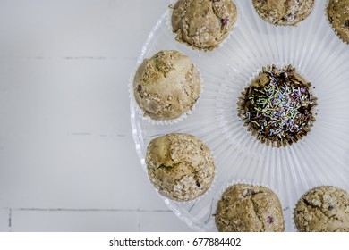 Muffins on glass cake stand on right side, view from above.