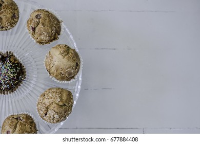 Muffins on glass cake stand on left side, view from above.