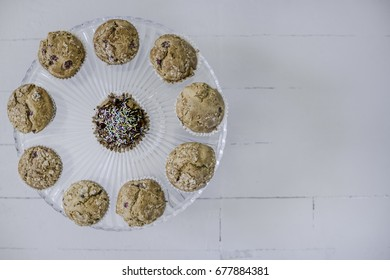 Muffins on glass cake-stand on left side, view from above.