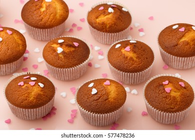 Muffins in paper forms and a lot of small sugar hearts on a mirrored background. Valentine's Day breakfast