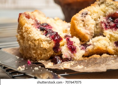 Muffins with red fruits jam fill on wooden counter top.