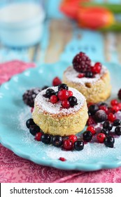 Muffins with ricotta and berries sprinkled with powdered sugar on a blue plate