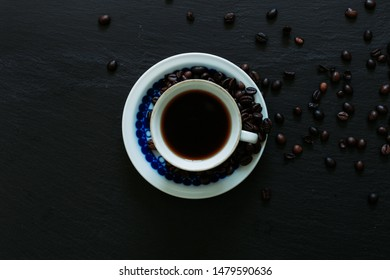 Mug of Arabic aroma taste with few coffee seeds on a black background - Top view and closeup of a black coffee on the table.