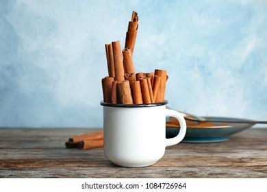 Mug with aromatic cinnamon sticks on wooden table
