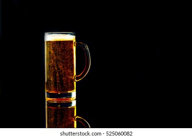 mug of beer with bubbles on a black background