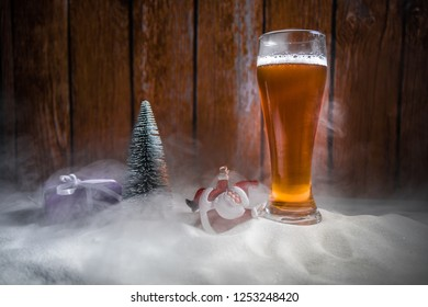 Mug of beer with Christmas decoration. Glass of light beer with foam in snow with creative New Year holiday artwork. Copy space