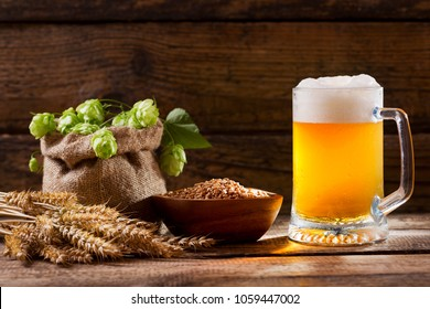Mug of beer with green hops, wheat ears and grains and on wooden table