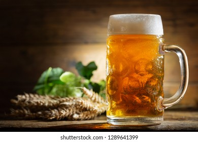 Mug of beer with green hops and wheat ears on wooden table