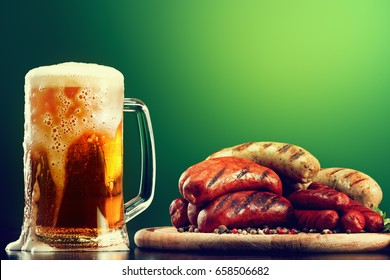 Mug of beer with grilled sausages on green background. Oktoberfest traditional drink and food in pub