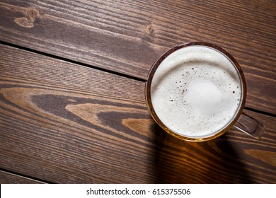 Mug of beer on an old wooden table. Top view