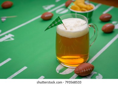 mug of beer on snack table decorated for superbowl party