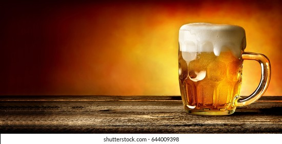 Mug of beer on timber table and orange background