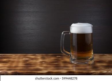 Mug of beer on wood surface. Dark background.
