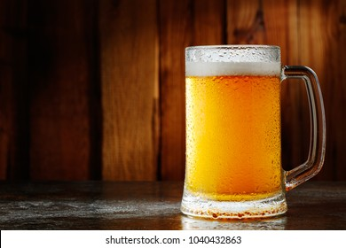 mug with beer on a wooden background