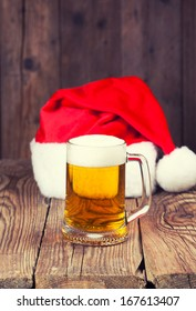 mug of beer with Santa's hat on wooden background