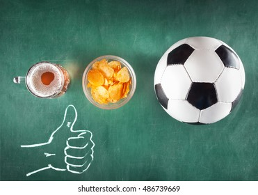 mug of beer with snack and soccer ball on green background. Thumb up.